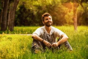 © Maksim Petrov / 123RF.com - Happy cheerful man sitting on a grass at the park, smiling and lost in thoughts