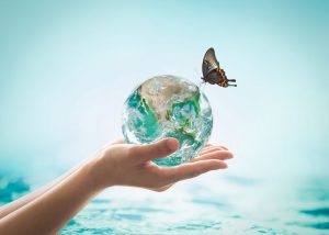 Planet in a hand with ocean and a butterfly