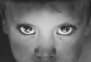 Boy depressed with a tear in the eyes
