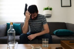 Man contemplting shooting self with gun with alcohol, depressed